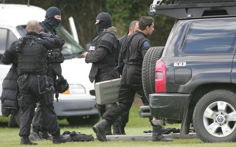 Armed police load equipment into vehicles in New Zealand. Photo: John Cowpland/Sunday Star-Times. Image may be subject to copyright.
